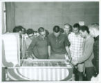 Students playing pinball machine, Harvey Mudd College