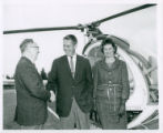 Three individuals standing near a helicopter, Pomona College