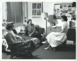 Three women, seated, dormitory room, Pomona College