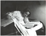 Scripps College student Dawn Gardner, studying in bed