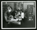 Three students reading books on top of bookcases in Denison Library, Scripps College