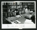 Three women study at a table in Denison Library, Scripps College