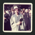 Scripps student wearing a green graduation gown and cap  proudly holds her diploma, Scripps College