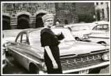Charles Protzman's wife standing in a parking lot, 1961-05