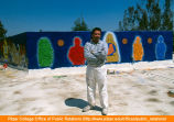 Yando Rios in front of serpent mural